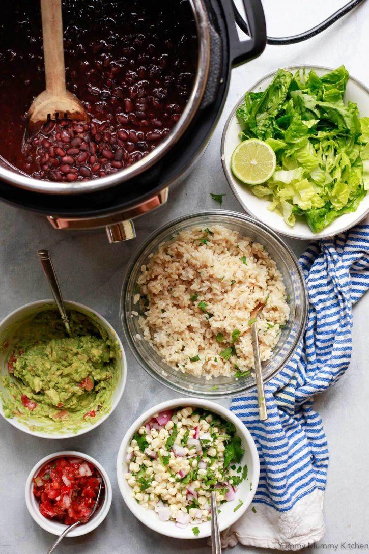 Vegetarian vegan Chipotle burrito bowl toppings sit on a countertop: cilantro lime brown rice, black beans, fresh corn salsa, Romaine lettuce, guacamole, and salsa.