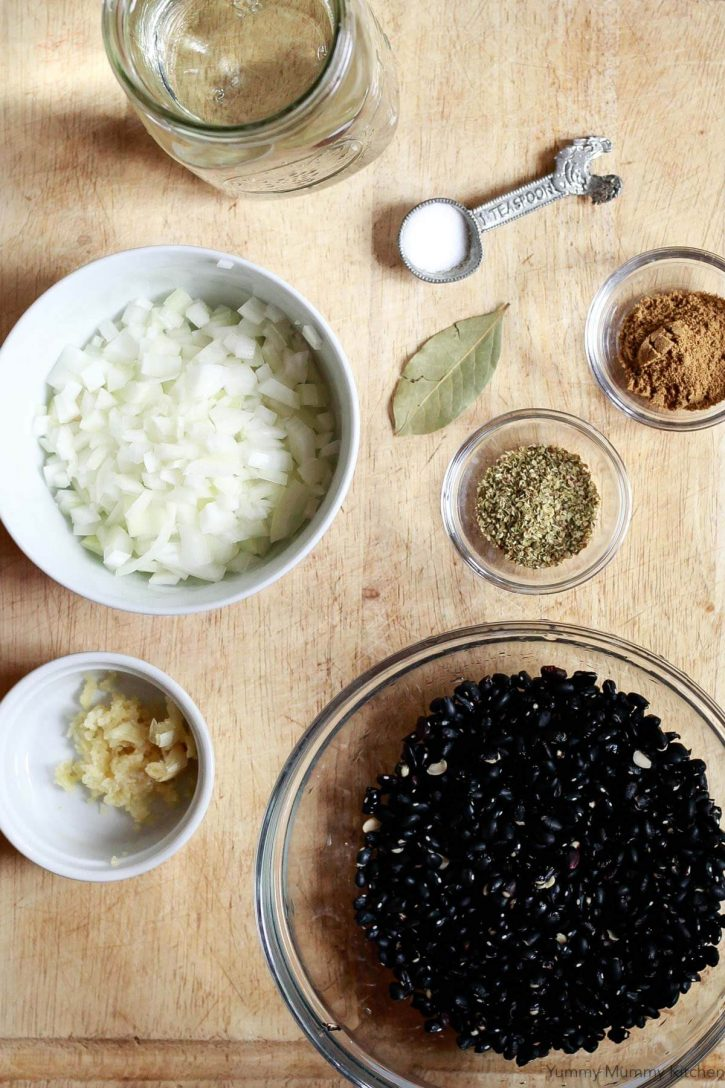 Ingredients for Instant Pot black beans on a cutting board include dried black beans, onion, garlic, oregano, bay leaf, cumin, salt, and water.