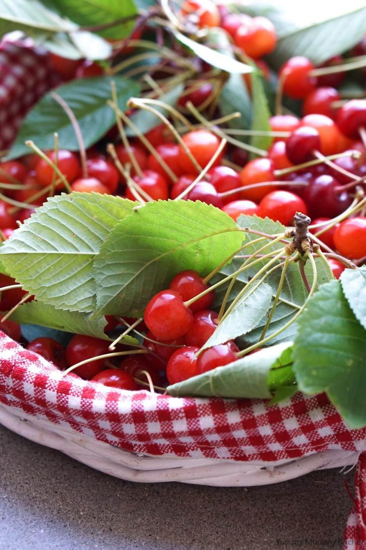 A red gingham basket filled with freshly picked cherries.
