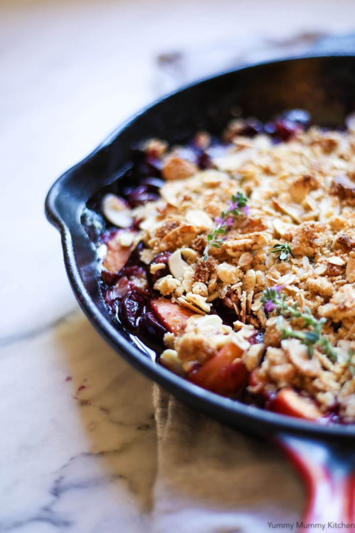 Bubbly fresh cherry and apricot crisp in a skillet topped with golden almond crisp topping.