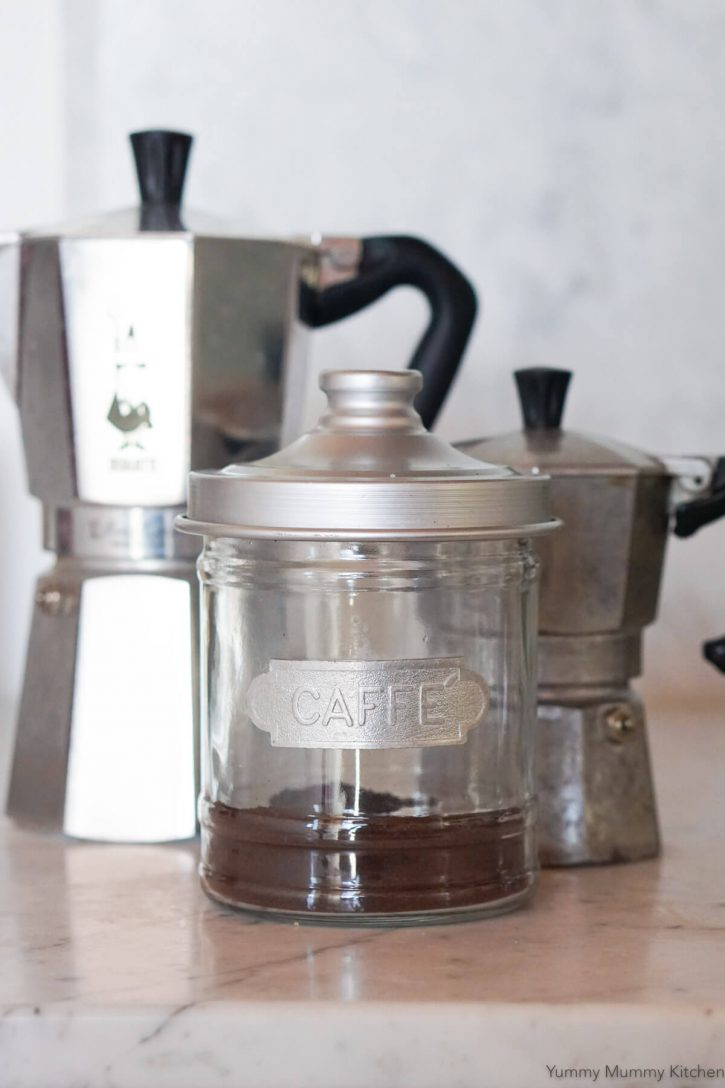 A glass canister of ground espresso coffee in the foreground with two Bialetti moka espresso makers in the background.