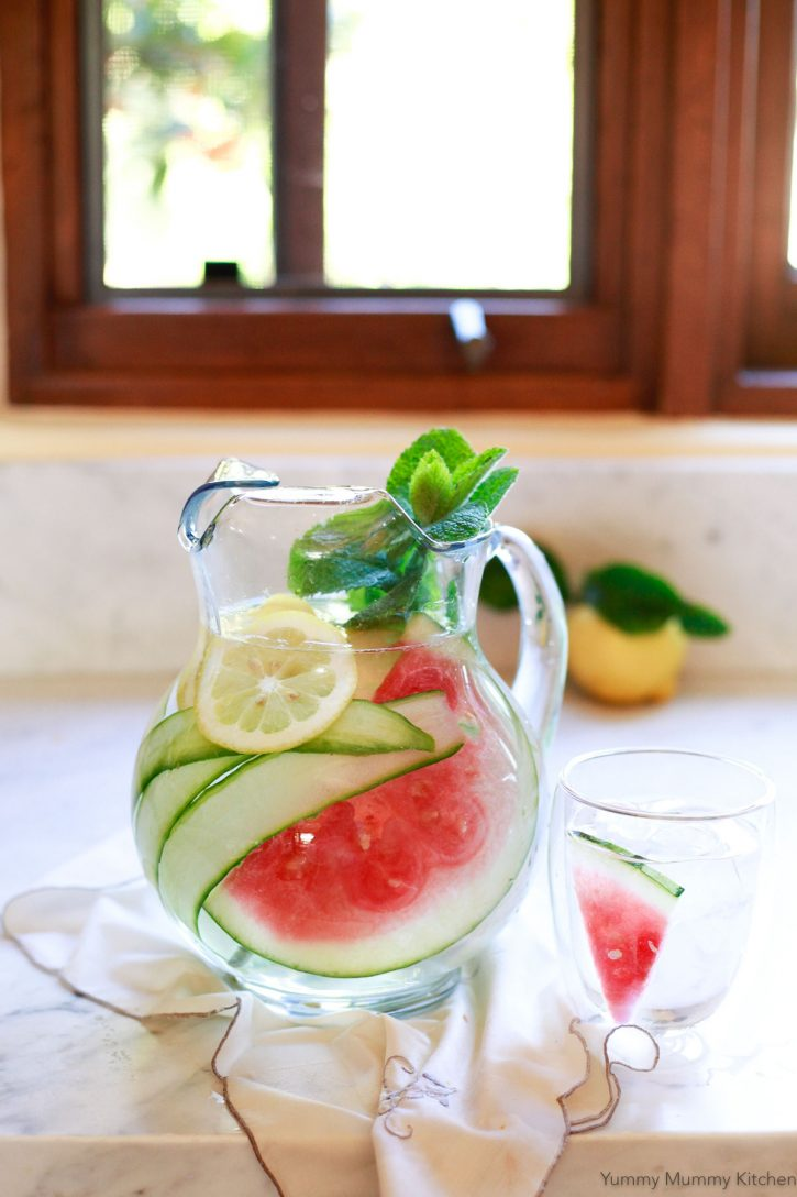 A glass pitcher with cucumber, watermelon, and lemon detox water on a white kitchen countertop.