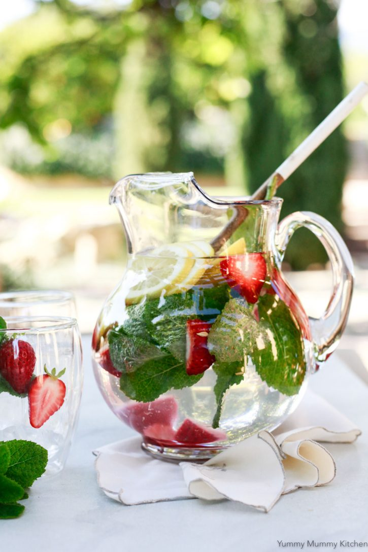 A beautiful glass pitcher filled with water, lemon slices, strawberries and mint. This is a great way to help detox from sugar.