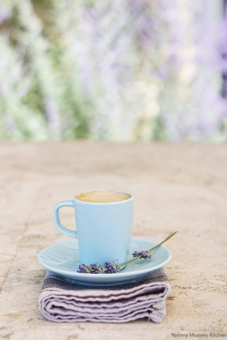 A small blue mug filled with a lavender latte sits on a saucer with fresh lavender sprig.