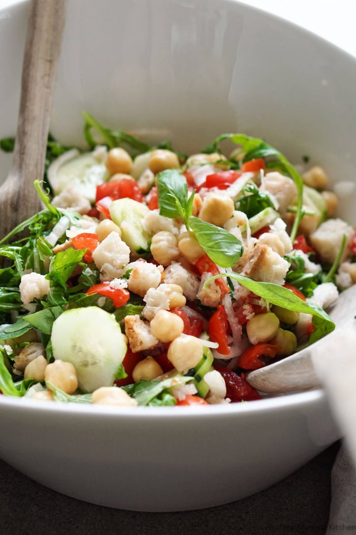 A bowl of panzanella salad with chickpeas and arugula. This photo was taken in Tuscany while making panzanella bread and tomato salad.