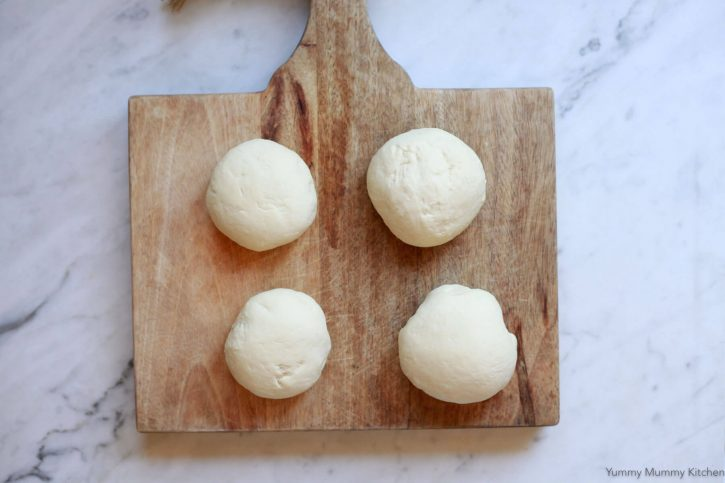 Four small balls of pizza dough resting on a wooden cutting board.