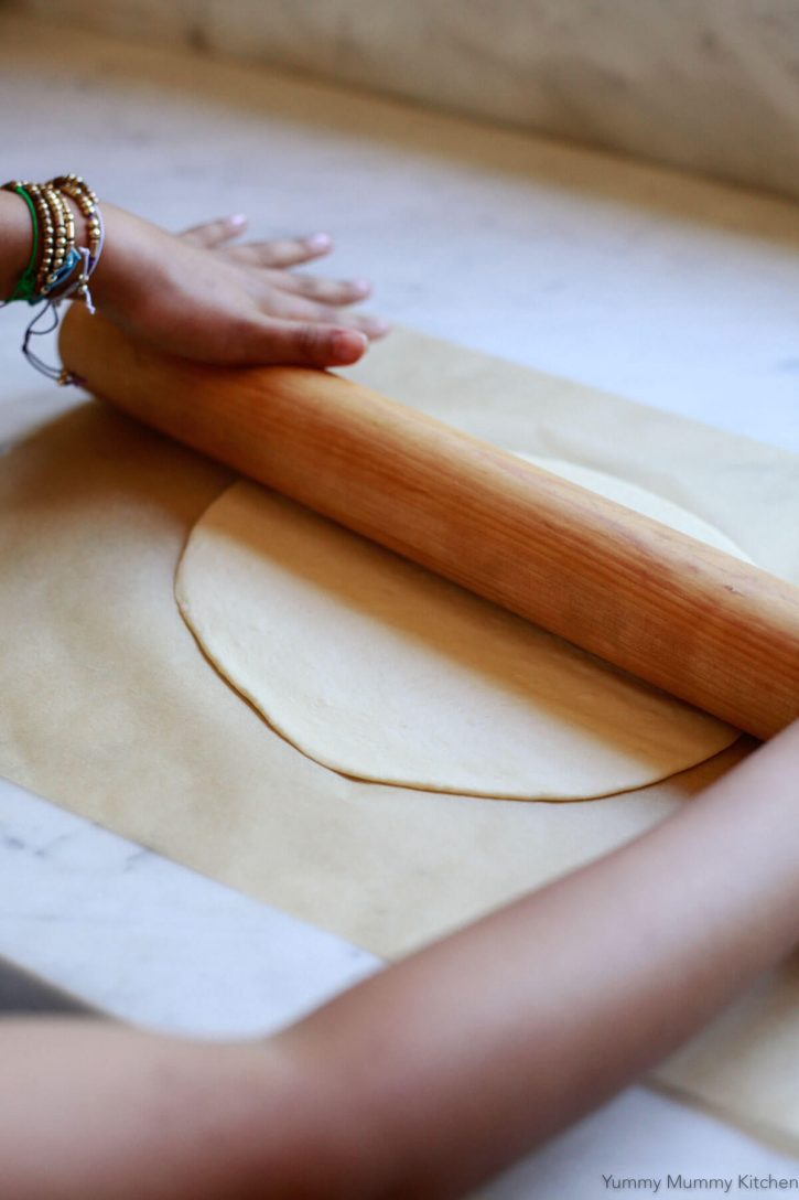 A child's hands roll a thin crust pizza dough with a wooden rolling pin.
