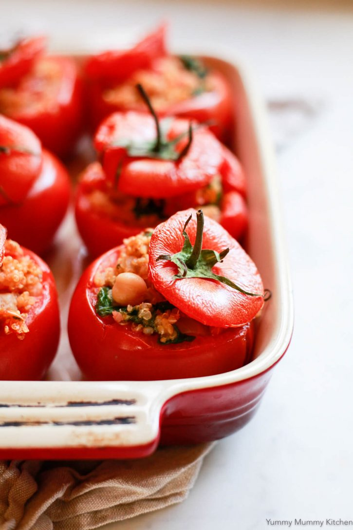 Tomatoes filled with chickpea quinoa baked in a casserole dish for a healthy vegan gluten free dinner.