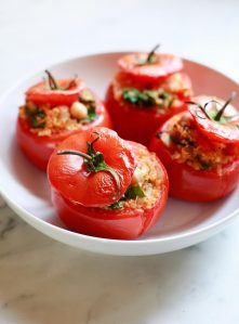 A dish filled with baked stuffed vegetarian tomatoes with quinoa and spinach.