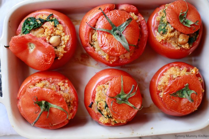 An overhead photo of quinoa stuffed tomatoes in a ceramic baking dish.