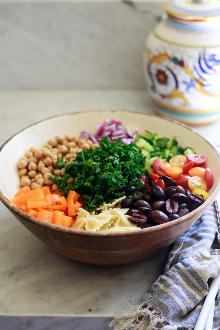 A wooden salad bowl filled with ingredients for a Greek vegan pasta salad.