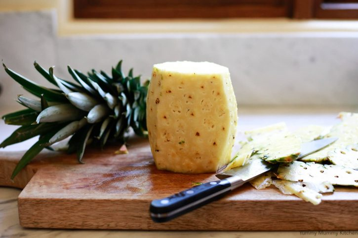 A whole fresh pineapple is peeled with a knife on a wooden cutting board.