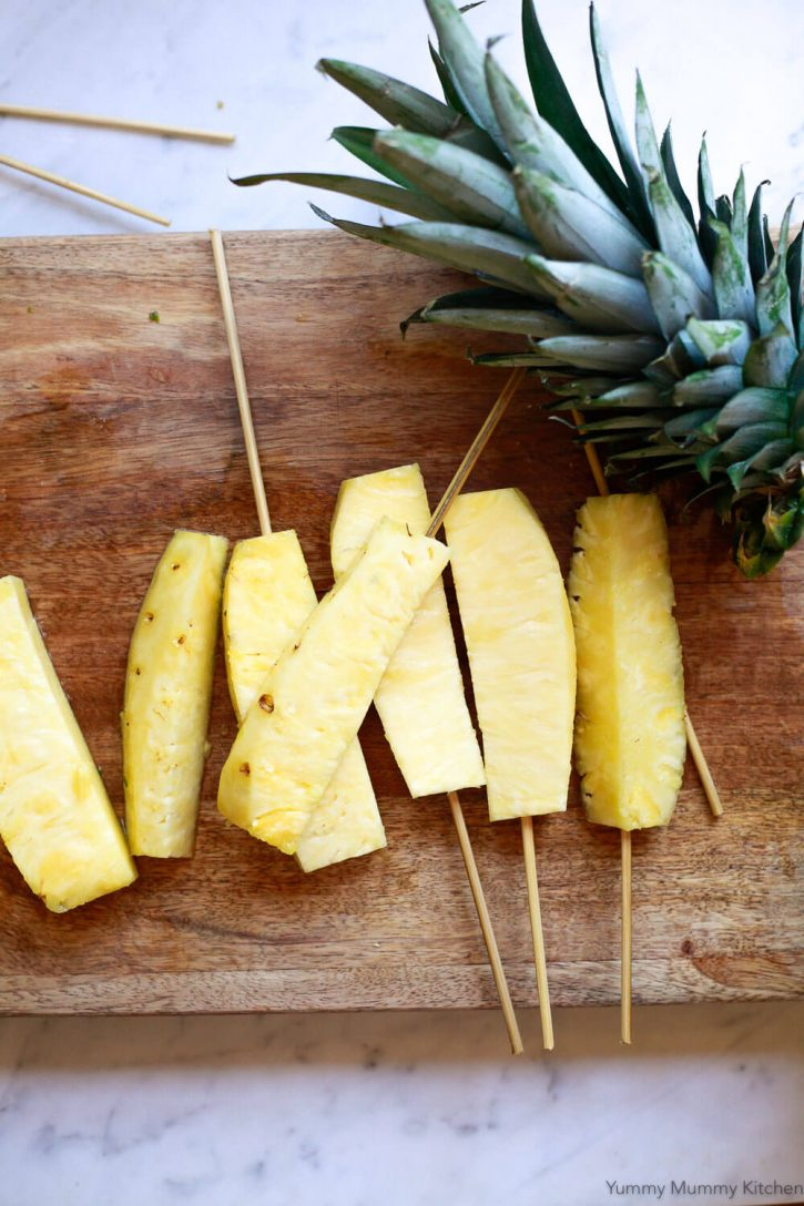 Freshly cut pineapple spears on skewers.