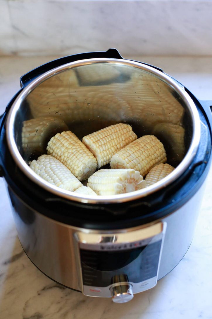 8 half-ears of shucked corn on the cob inside an Instant Pot pressure cooker with a little water.