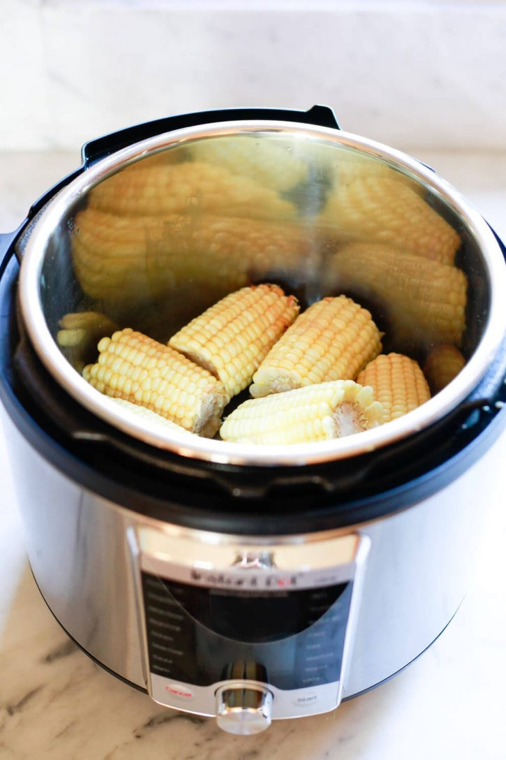 Perfectly cooked yellow corn on the cob inside an Instant Pot just after pressure cooking.