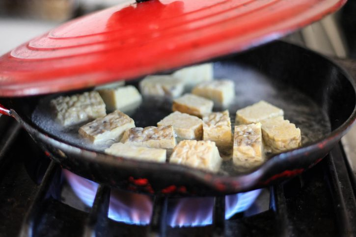 Cubed tempeh steams in a skillet.