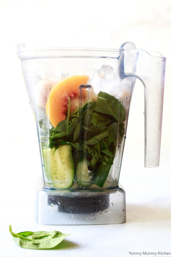 Cucumber, spinach, coconut water, and frozen peaches and banana in a Vitamix blender.