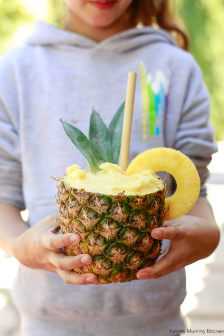 A girl holds a pineapple smoothie served in a pineapple. This healthy pineapple smoothie recipe is vegan an made with mango and banana.