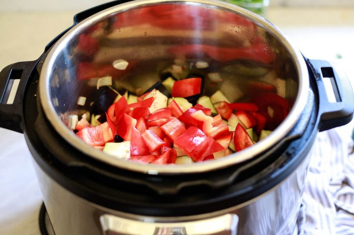 Red bell peppers, eggplant, and onions in an Instant Pot to make ratatouille.
