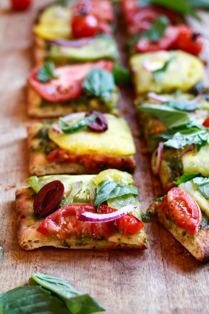 Slices of vegetarian and vegan pesto pizza topped with heirloom tomato slices, red onion, basil, and Kalamata olives.