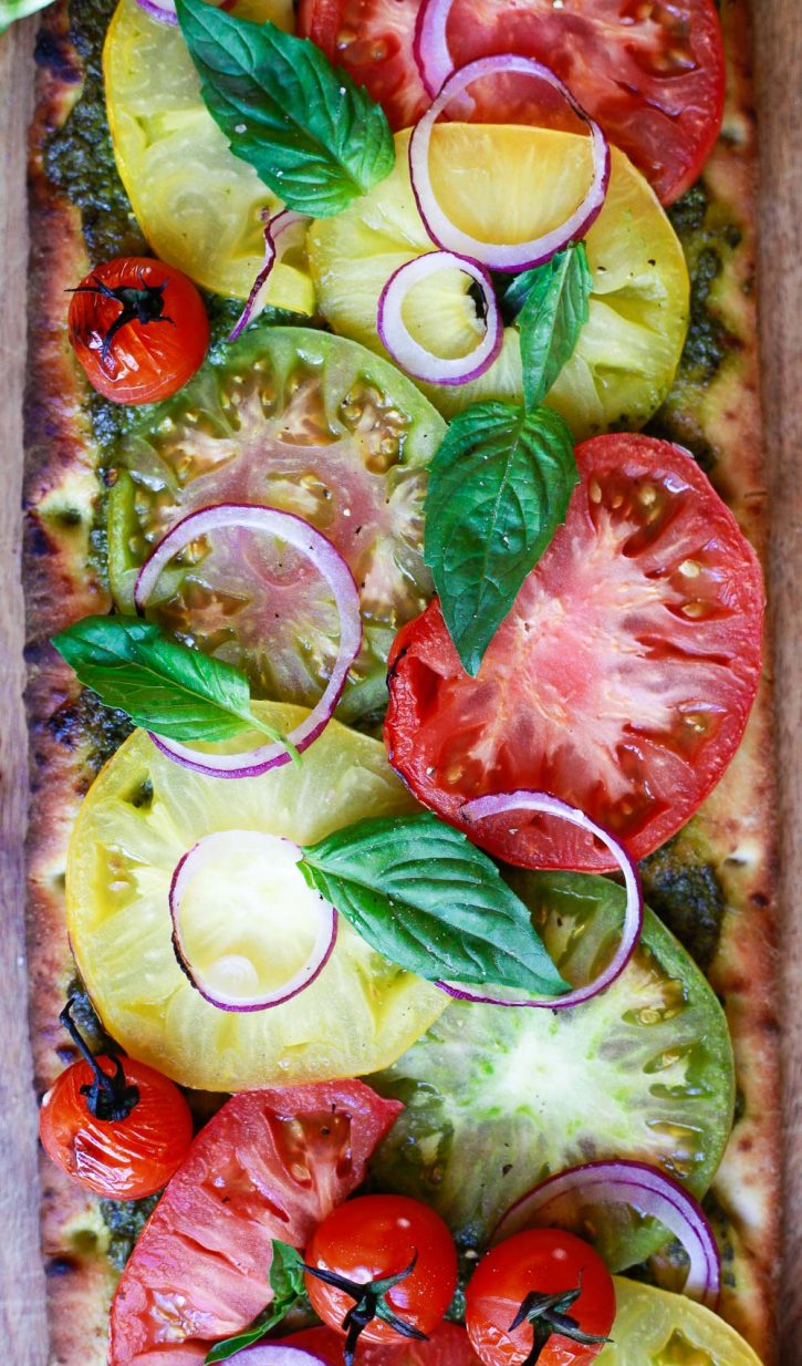 Colorful red, yellow, and green heirloom tomato slices on a pesto pizza.