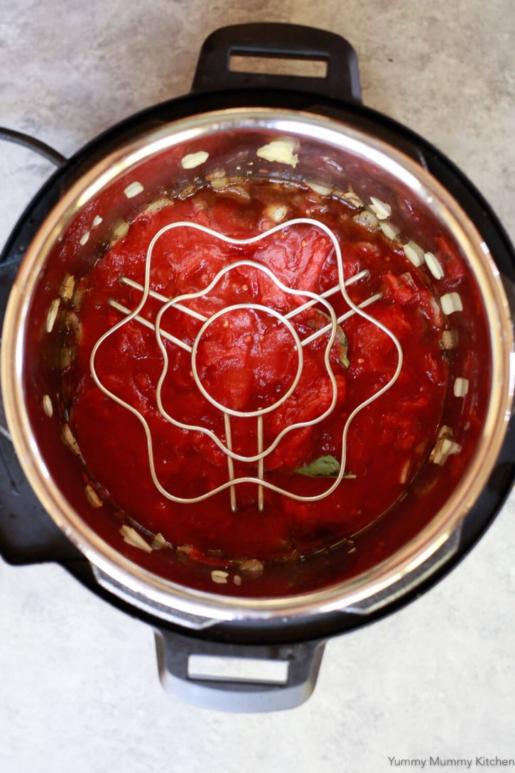 How to make Instant Pot spaghetti sauce. All the ingredients for Instant Pot spaghetti sauce are in a pressure cooker. A trivet is on top to cook a spaghetti squash with the pot in pot method.
