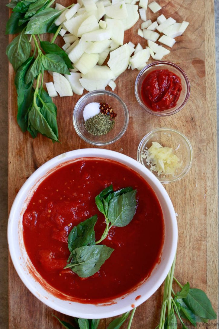 The ingredients for an easy simple Instant Pot spaghetti sauce on a cutting board: tomatoes, spices, garlic, onion, tomato paste, and fresh basil.