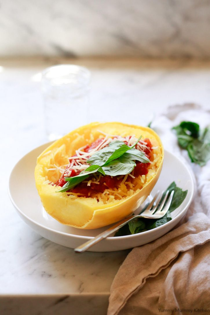 Half an Instant Pot cooked spaghetti squash with spaghetti sauce and fresh basil in a white bowl with a gold fork on a kitchen counter.