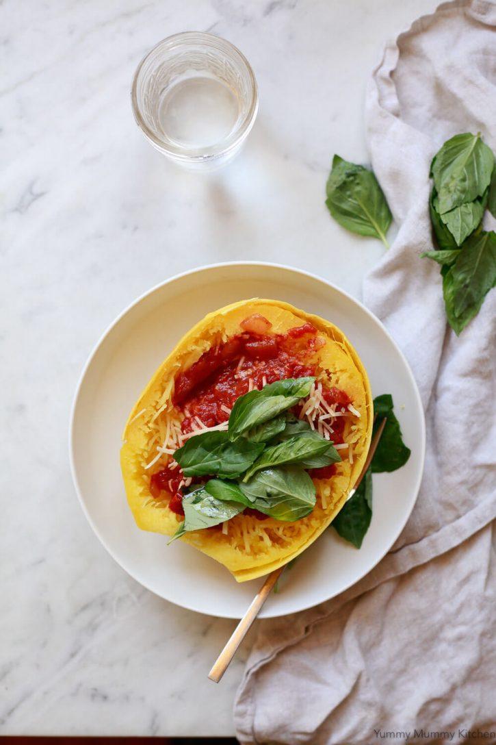 Instant Pot spaghetti squash half topped with tomato basil spaghetti sauce.
