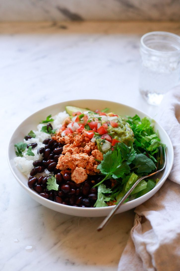 A vegan burrito bowl with black beans, rice, chipotle sofritas, guacamole and salsa.