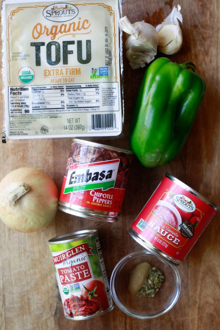 The ingredients for sofritas sit on a wooden board and include tofu, garlic, green bell pepper, tomato sauce, chipotle peppers, tomato paste, oregano and cumin, and a yellow onion.