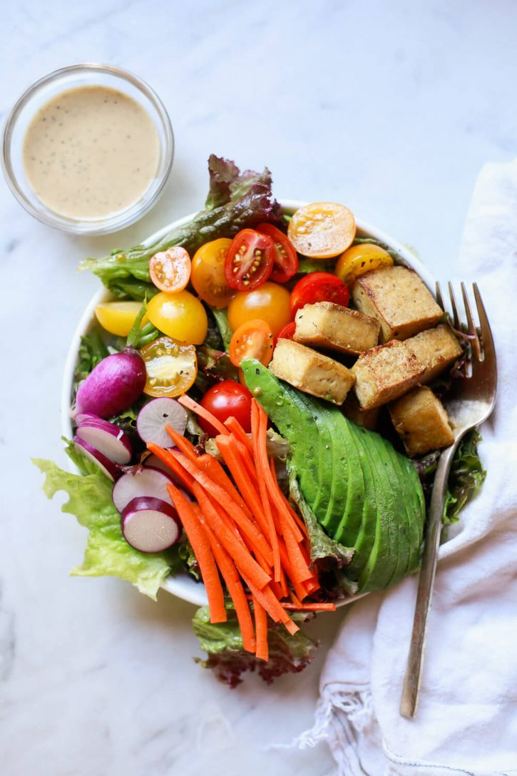 A beautiful healthy salad with crispy baked tofu cubes, avocado, carrots, purple radish, tomato, and greens.