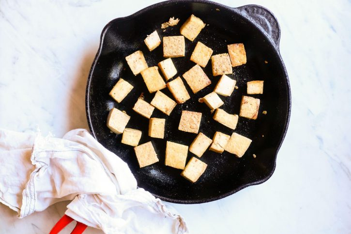 Crispy pan fried tofu cubes in a le Creuset skillet.