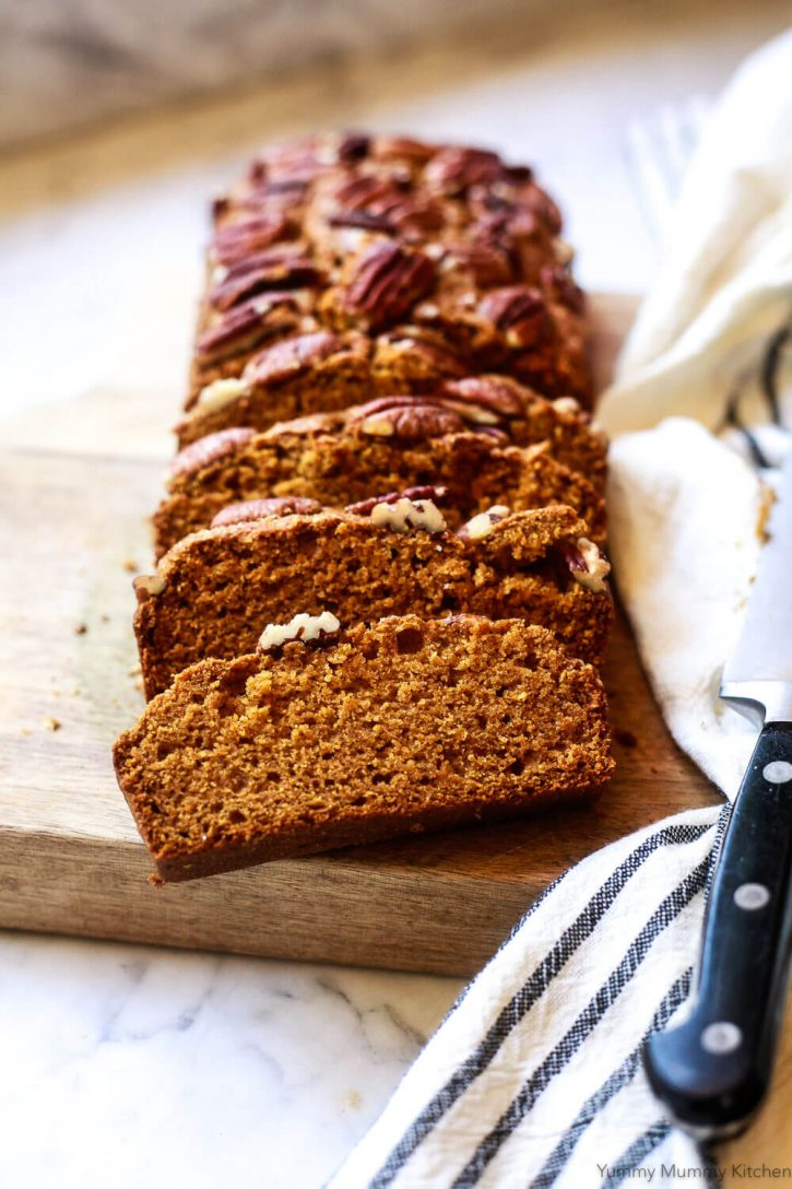 A loaf of healthy, dairy free, eggless whole wheat vegan pumpkin bread sliced on a cutting board.
