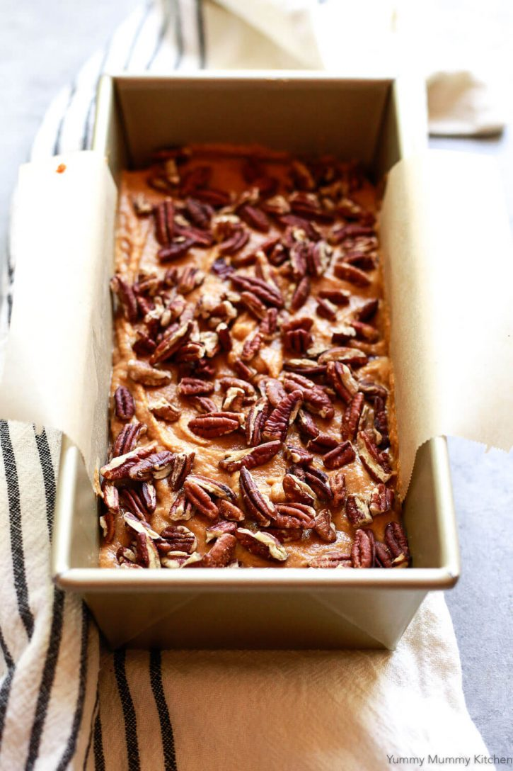 Pumpkin bread batter is smoothed into a loaf pan and topped with pecans.