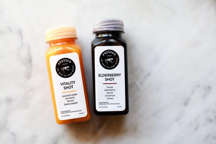 Wellness shots from Pressed Juicery on a marble countertop. Turmeric Vitality shot and Elderberry shot.