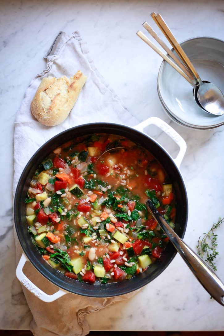 A white Staub cocotte pot filled with colorful Italian vegetable soup with white beans, kale, and farro.