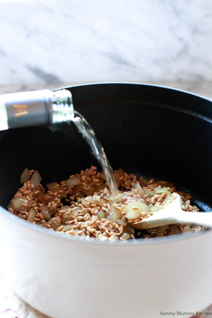 A splash of white wine is added to farro, onions, and garlic in a Staub pot to make farrotto.