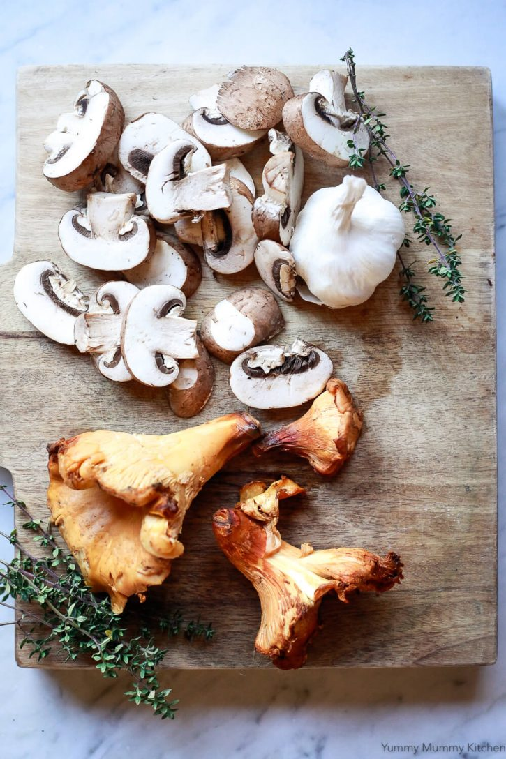 Wild Chanterelle mushrooms, Baby Bella mushrooms, garlic, and thyme on a cutting board before making farro risotto.