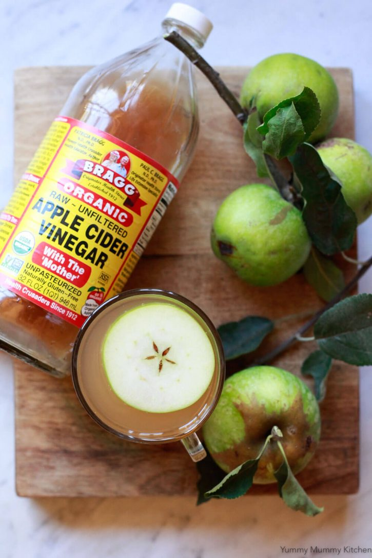 A bottle of Bragg apple cider vinegar sits on a cutting board next to hot apple cider vinegar detox drink.
