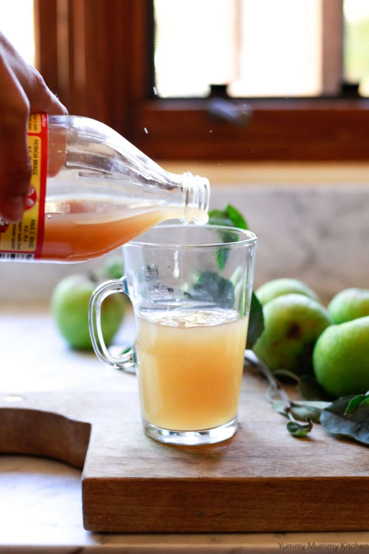 A bottle of Bragg apple cider vinegar is poured into a hot mug of steaming water and apple cider to make an apple cider vinegar detox drink.