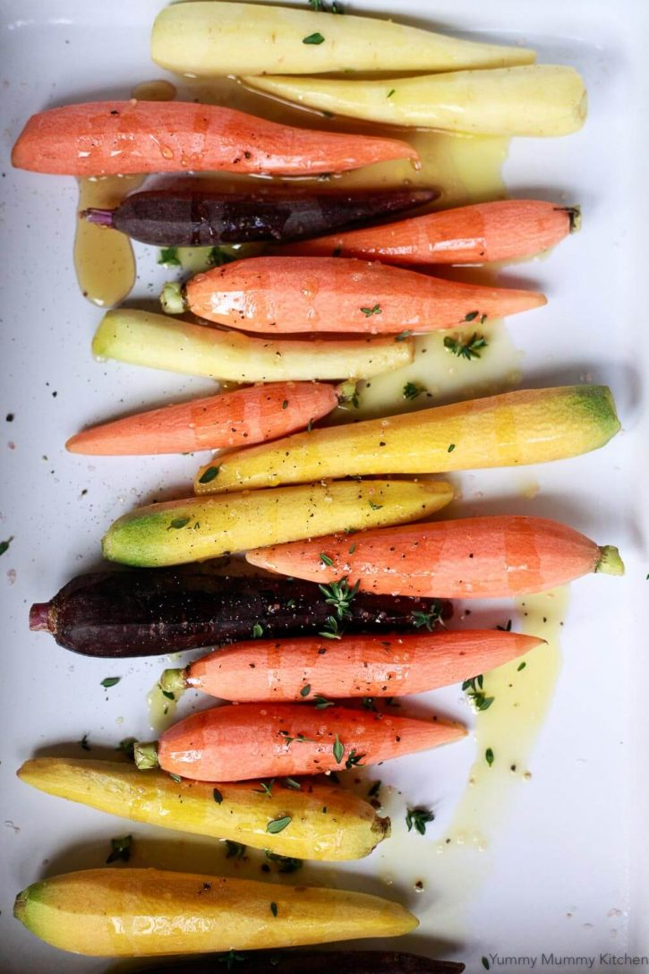 Whole rainbow carrots in a baking dish are coated with olive oil, maple syrup, salt and pepper, and fresh thyme and are ready for the oven.