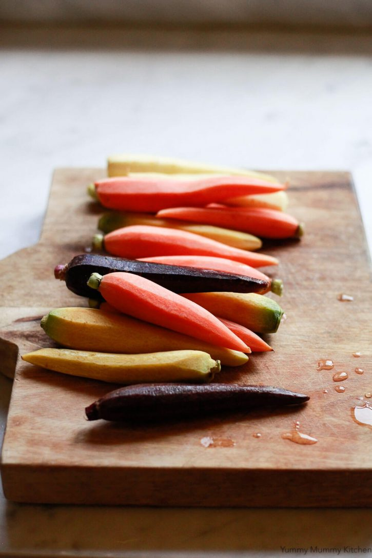 Trader Joe's rainbow carrots, Les Petites Carrots of Many Colors, on a cutting board to make roasted whole carrots.