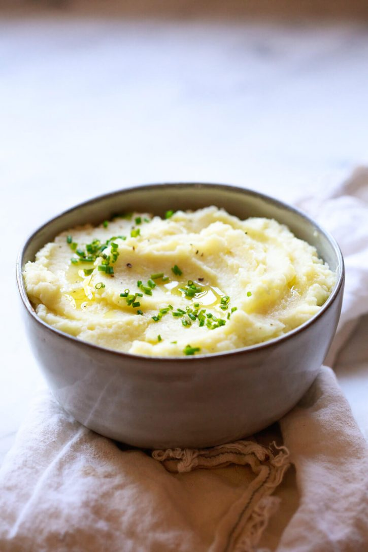 "A bowl of mashed cauliflower garnished with chives on a marble countertop. Cauliflower ""mashed potatoes"" are a creamy and cozy healthier side dish perfect for the holidays or any day. This garlic cauliflower mash recipe is keto and vegan friendly."
