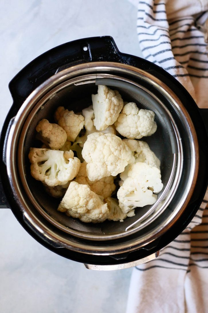 Large cauliflower florets in a steamer basket inside an Instant Pot pressure cooker.