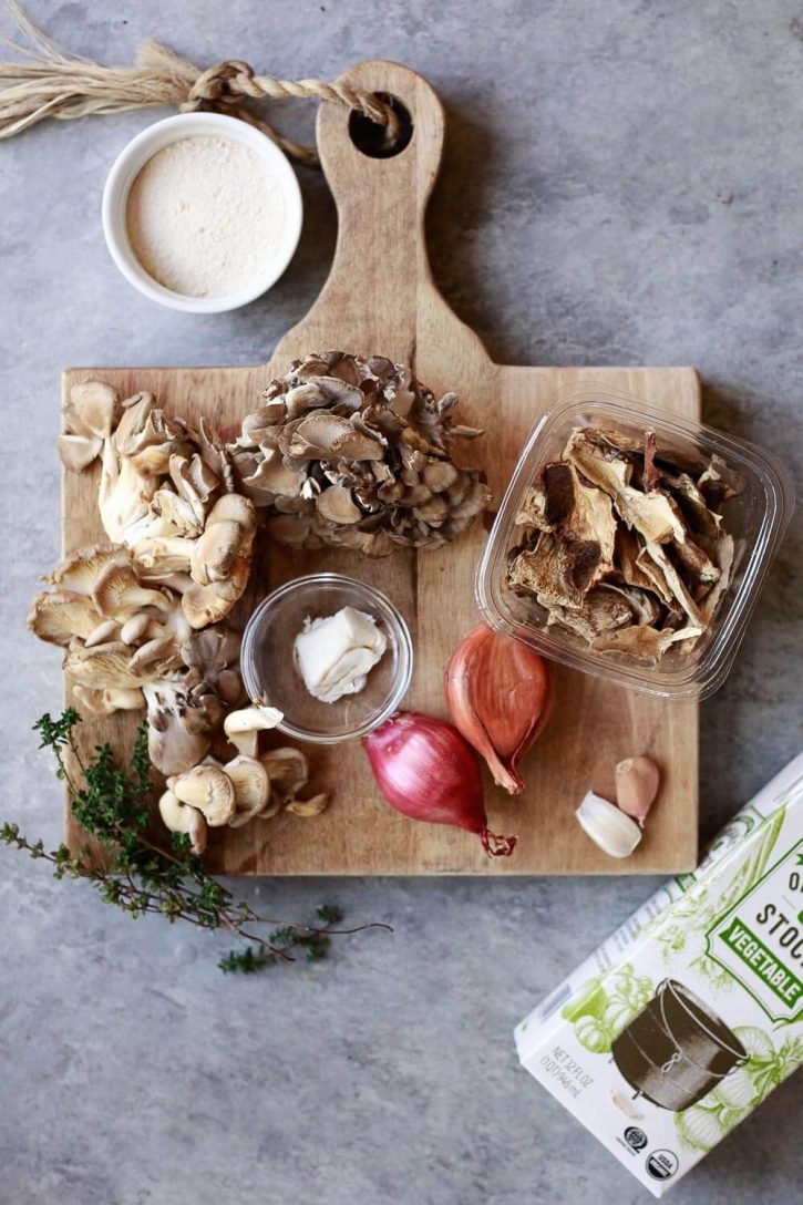 Ingredients for vegan mushroom gravy are set on a cutting board. Dried and fresh mushrooms, shallots, butter, flour, and vegetable stock.