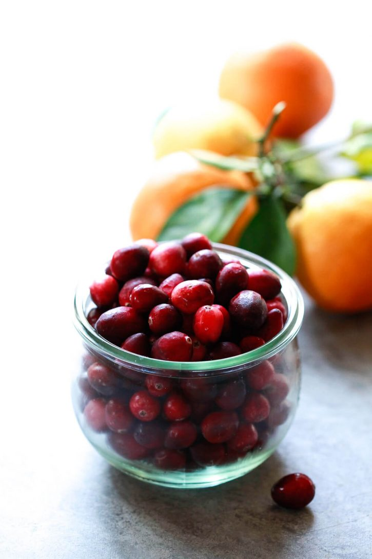 A bowl of fresh cranberries with oranges in the background. These are the main ingredients in a Cranberry Orange Sauce Recipe.