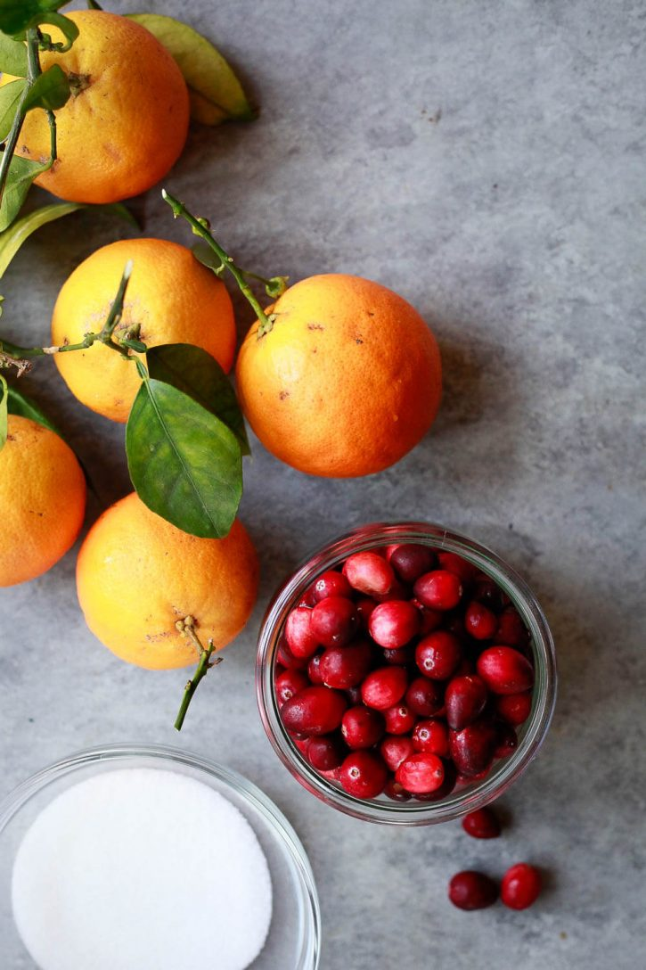 Oranges, fresh cranberries, and zero carb keto sugar free monk fruit sweetener on a countertop. These are the ingredients for a sugar free or keto cranberry sauce.