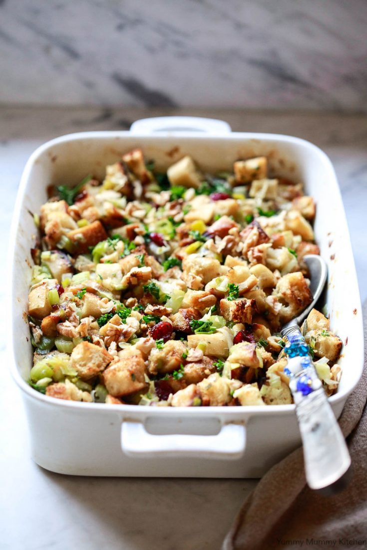 Classic baked stuffing is filled with sourdough baguette cubes, leeks, celery, fresh herbs, cranberries and pecans. This vegetarian & vegan baked stuffing recipe is perfect for Thanksgiving or Christmas.
