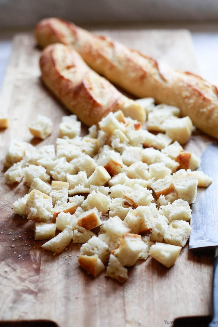 Two baguettes are cut into cubes for Thanksgiving stuffing.